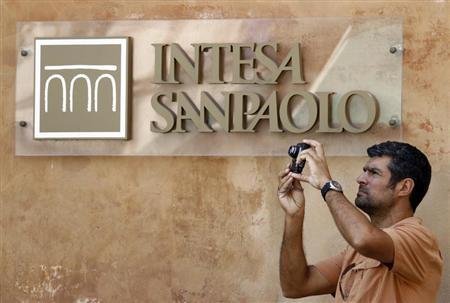A man takes a picture in front of Intesa Sanpaolo bank in downtown Rome