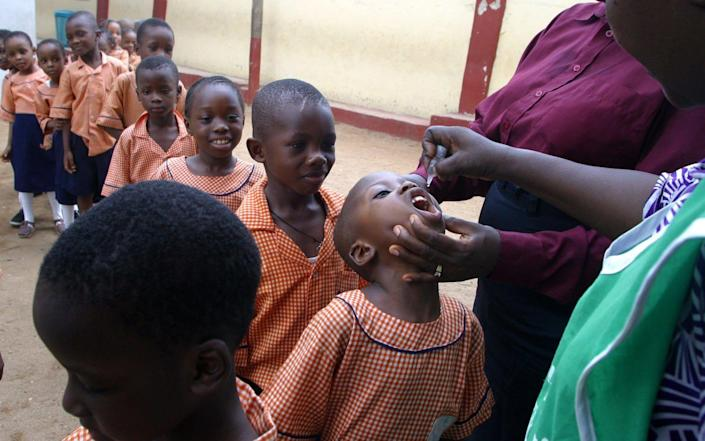 Health workers vaccinate children with drops of polio vaccines in Lagos, Nigeria - GEORGE OSODI/AP