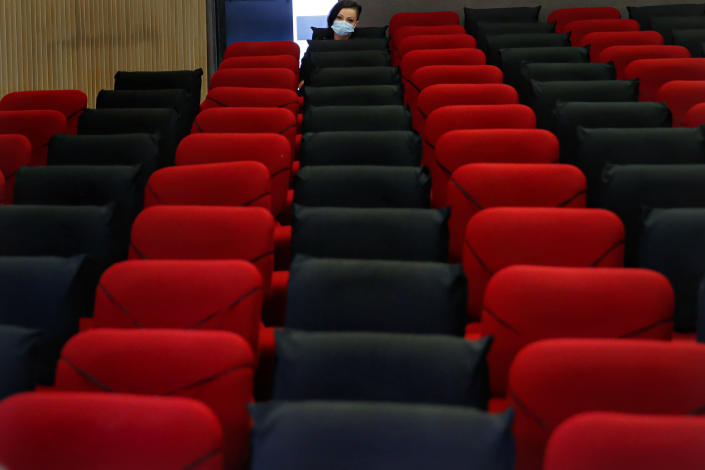 """Tedy Ursuleanu, a survivor of the Colectiv nightclub fire, waits before an interview with the Associated Press at the Elvire Popesco cinema in Bucharest, Romania, Monday, April 12, 2021. The Oscar-nominated Romanian documentary film """"Collective"""" follows a group of journalists delving into the state of health care in the eastern European country in the wake of a deadly 2015 nightclub fire that left dozens of burned victims in need of complex treatment. What they revealed was decades of deep-rooted corruption, a heavily politicized system scarily lacking in care. (AP Photo/Vadim Ghirda)"""