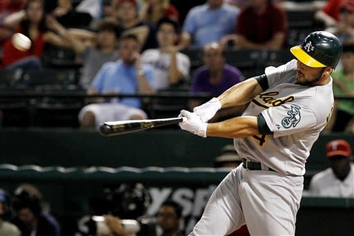 Oakland Athletics' George Kottaras (14) connects for a solo home run off of Texas Rangers' Mark Lowe in the 10th inning of a baseball game, Tuesday, Sept. 25, 2012, in Arlington, Texas. The Athletics won 3-2. (AP Photo/Tony Gutierrez)