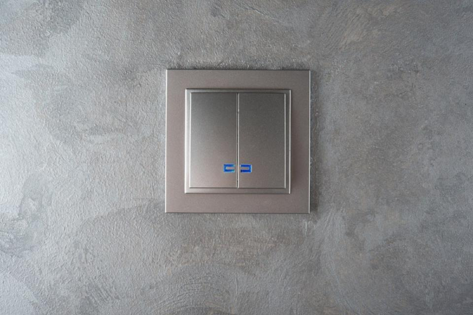 silver light switch plate on gray wall