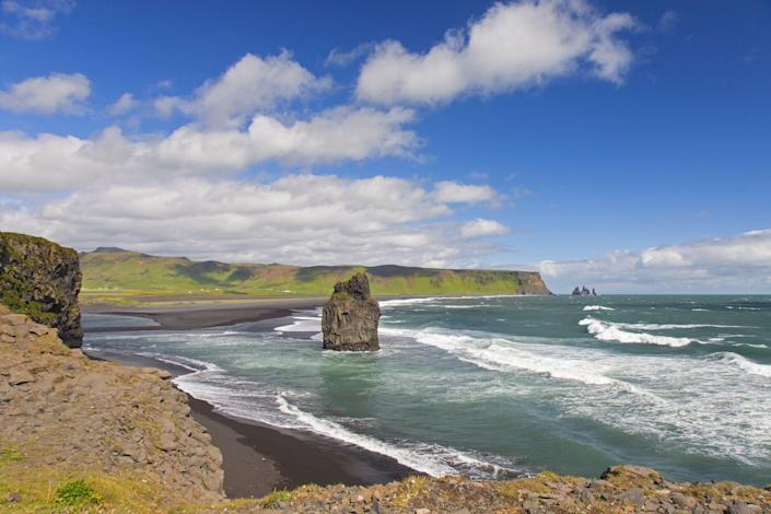 A big rock juts out from the ground in the sea along a beach in Iceland