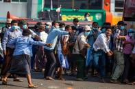 Military supporters use slingshots against pro-democracy protesters during a military support rally in Yangon