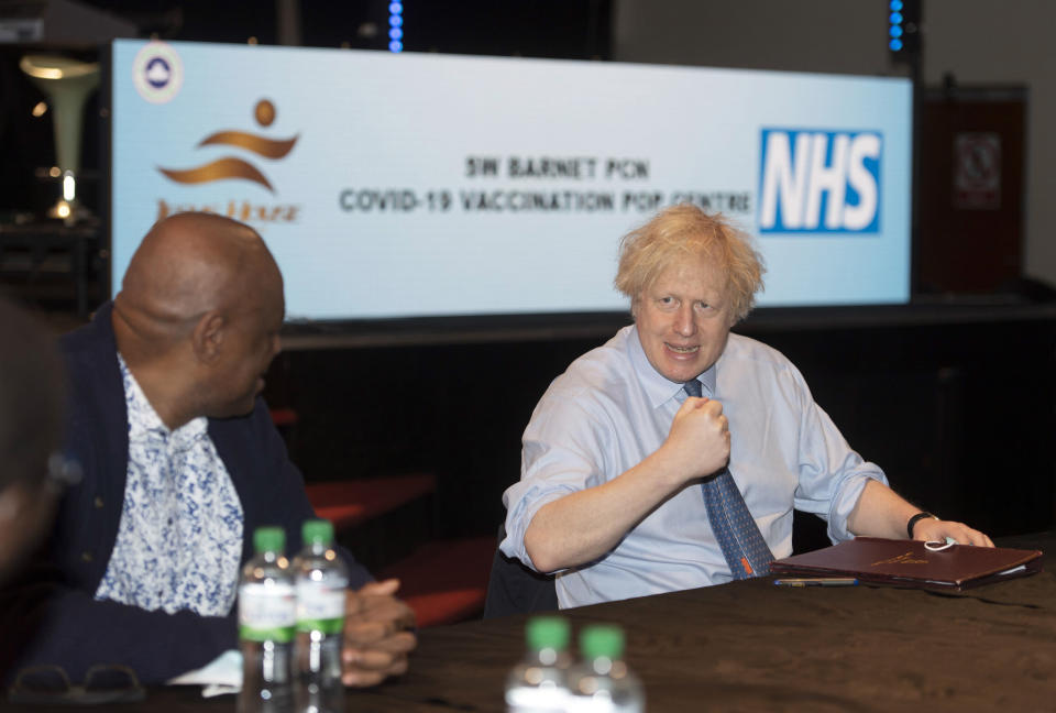 Britain's Prime Minister Boris Johnson talks to church leaders during a visit to a vaccination centre at Jesus House for All The Nations, in North London, Sunday March 7, 2021. (Geoff Pugh/Pool via AP)
