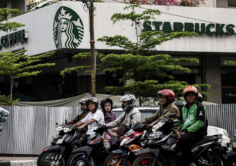 Indonesians wait at the traffic lights outside a branch of Starbucks in central Jakarta on January 15, 2016, a day after the cafe was hit as part of attacks claimed by the Islamic State group (AFP Photo/Manan Vatsyayana)
