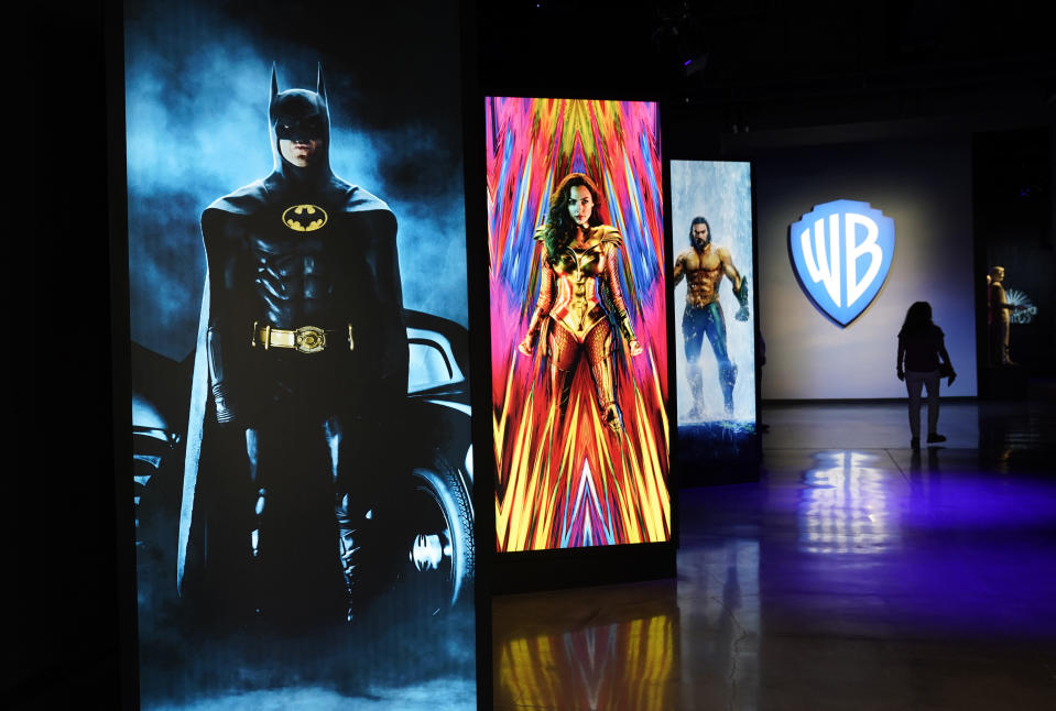 """A visitor walks past portraits of DC Comics superheroes as she enters the """"Action and Magic Made Here"""" interactive experience at the Warner Bros. Studio Tour Hollywood media preview on June 24, 2021, in Burbank, Calif. (AP Photo/Chris Pizzello)"""