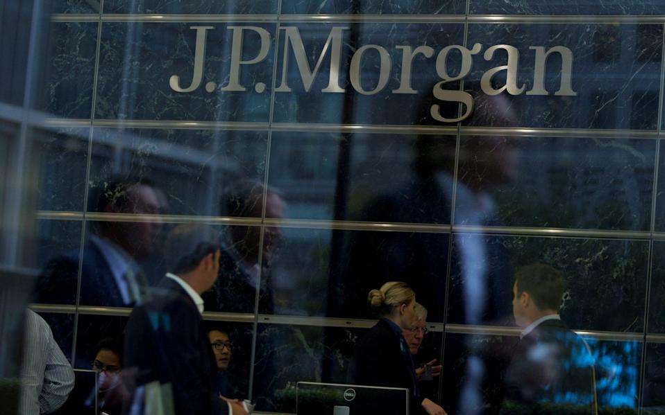 Workers are reflected in the windows of the Canary Wharf offices of JP Morgan in London - Neil Hall/Reuters
