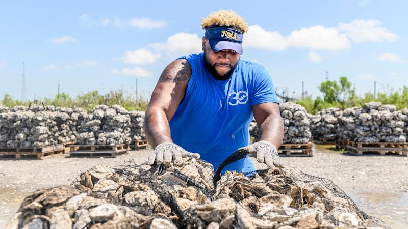 Demonte Sawyer sets collected bags of oyster shells onto pallets, which they'll use to put them into the water at the Coalition to Restore Coastal Louisiana oyster shell collection center in Buras, Louisiana., on May 21, 2019. (Photo: Emily Kask for HuffPost)