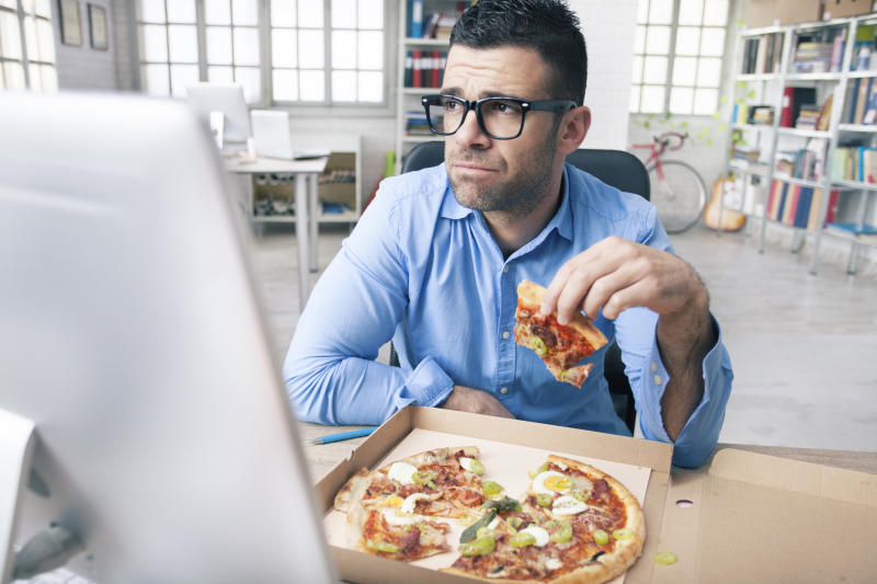 Tired young businessman holding slice of pizza and looking away. Man with eyeglasses and blue shirt. Monitor and pizza in box on desk. Windows, shelves with boxes and folders, desk with computer, bike and guitar as background.
