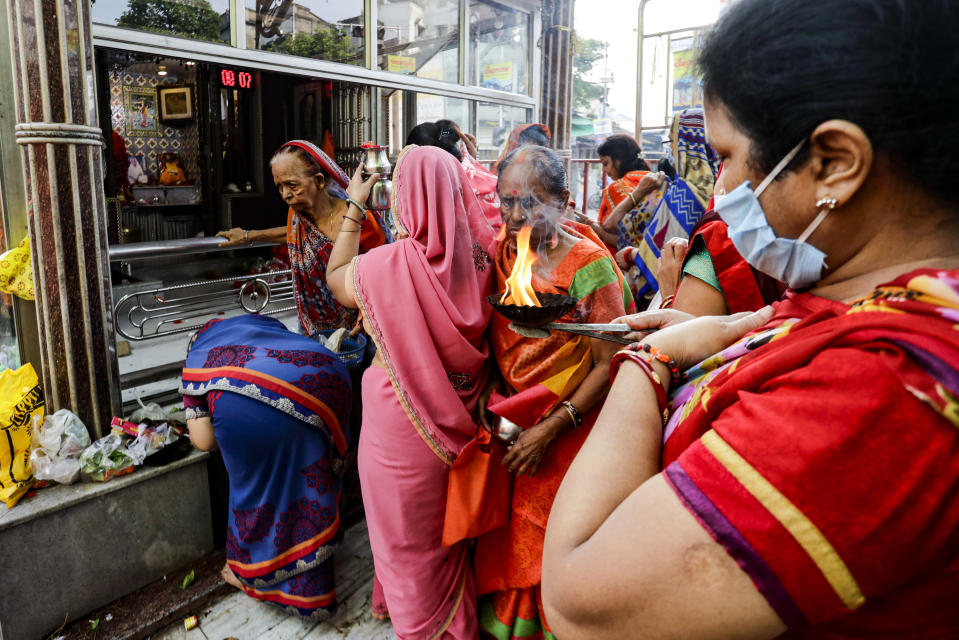 FILE- In this Saturday, Oct. 17, 2020, file photo, Hindu women, some wearing face masks to prevent the spread of the coronavirus, perform rituals outside a temple in Kolkata, India. Weeks after India fully opened up from a harsh lockdown and began to modestly turn a corner by cutting new infections by near half, a Hindu festival season is raising fears that the disease could spoil the hard-won gains. Health experts worry the festivals can set off a whole new cascade of infections, further testing and straining India's battered health care system. (AP Photo/Bikas Das, File)