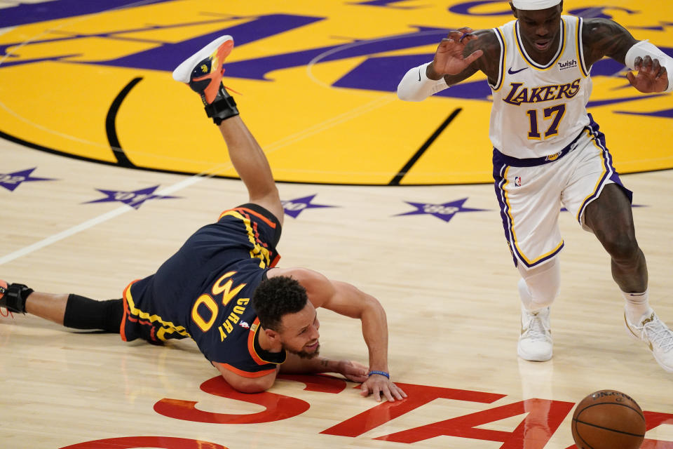 Golden State Warriors guard Stephen Curry, left, falls and looses the ball while under pressure from Los Angeles Lakers guard Dennis Schroder during the first half of an NBA basketball game Sunday, Feb. 28, 2021, in Los Angeles. (AP Photo/Mark J. Terrill)