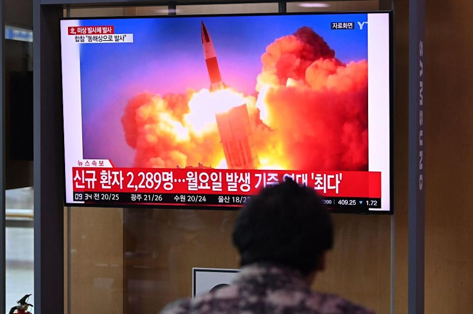 People watch a television news broadcast showing file footage of a North Korean missile test, at a railway station in Seoul.