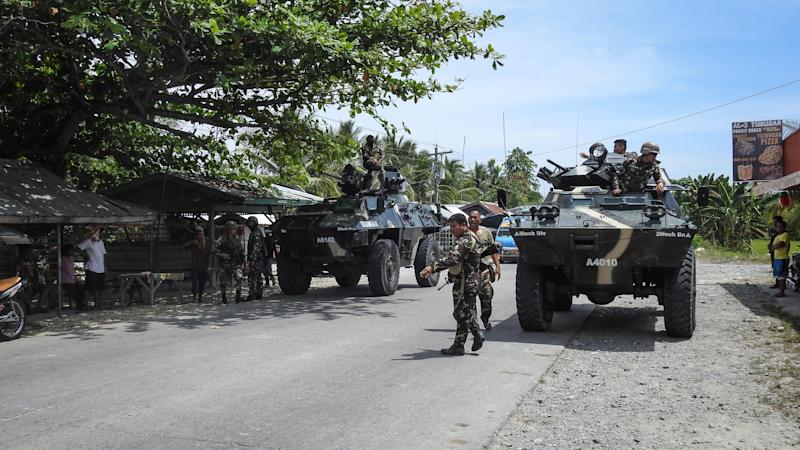 File Photo: This photo taken on March 8, 2018 shows Philippine soldiers standing next to their armoured personnel carriers as they man a checkpoint along a highway in Datu Saudi Ampatuan town, Maguindanao province on the southern island of Mindanao. (Photo: FERDINANDH CABRERA/AFP via Getty Images)