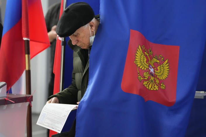 A man examines his ballot during the State Duma, the Lower House of the Russian Parliament and local parliament elections at a polling station in St. Petersburg, Russia, Sunday, Sept. 19, 2021. The head of Russia's Communist Party, the country's second-largest political party, is alleging widespread violations in the election for a new national parliament in which his party is widely expected to gain seats. (AP Photo/Dmitri Lovetsky)