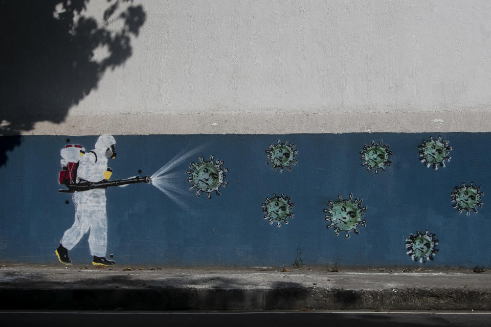 RIO DE JANEIRO, BRAZIL - JUNE 08: A view of a wall with a graffiti depicting a cleaner in protective gear spraying viruses with the face of President Jair Bolsonaro is seen in Estacio neighborhood amidst the coronavirus (COVID-19) pandemic on June 8, 2020 in Rio de Janeiro, Brazil. (Photo by Bruna Prado/Getty Images)