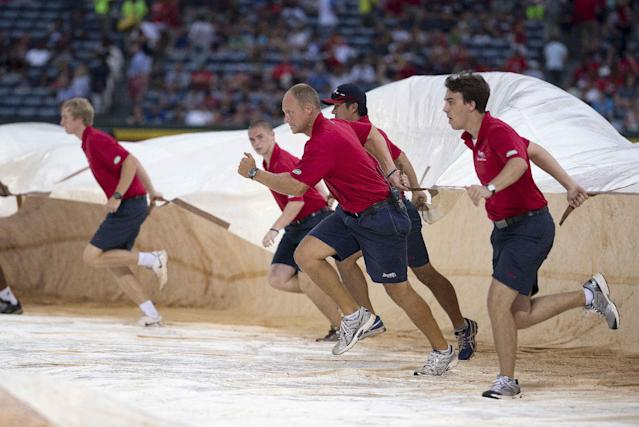 Atlanta Braves grounds crew members race to cover the infield before a downpour that delayed the start of the Braves' baseball game against the Washington Nationals on Saturday, Aug. 9, 2014, in Atlanta. (AP Photo/John Bazemore)