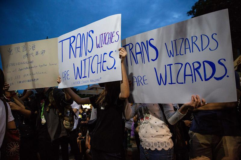 Anti-government protesters in Bangkok hold signs calling out J.K. Rowling's transphobic Twitter comments as they take part in a Harry Potter themed rally in front of Democracy Monument on Aug. 3. (Photo: Lauren DeCicca via Getty Images)