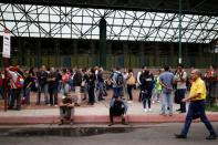 FILE PHOTO: People wait for transportation outside a closed metro station during a blackout in Caracas