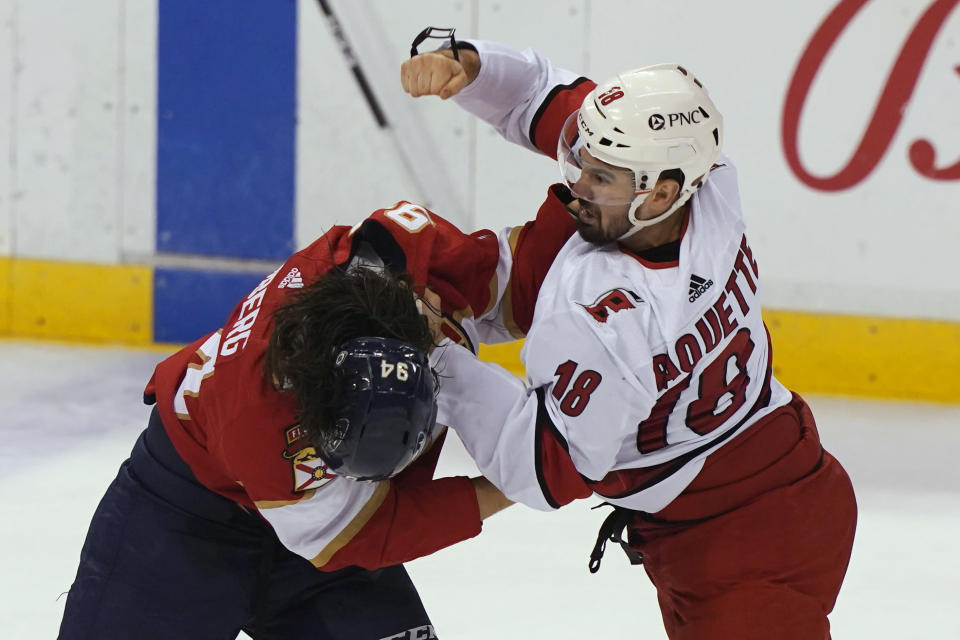 Carolina Hurricanes center Cedric Paquette (18) and Florida Panthers left wing Ryan Lomberg (94) fight during the first period at an NHL hockey game Thursday, April 22, 2021, in Sunrise, Fla. (AP Photo/Marta Lavandier)