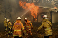 FILE - In this Jan. 23, 2020, file photo, firefighters battle the Morton Fire as it burns a home near Bundanoon, Australia. Australia has sweltered through its fourth-hottest year on record despite the usually cooling impact in recent months of the La Nina climate pattern, the nation's weather bureau said on Friday, Jan. 8, 2021. (AP Photo/Noah Berger, File)