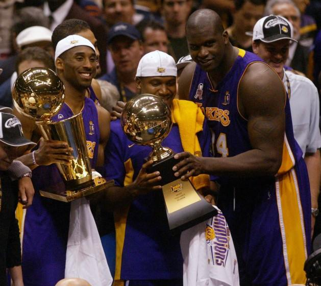 Lakers Kobe Bryant holds up the NBA Trophy as Lindsey Hunter and Shaquille O'Neal hold the MVP Trophy.