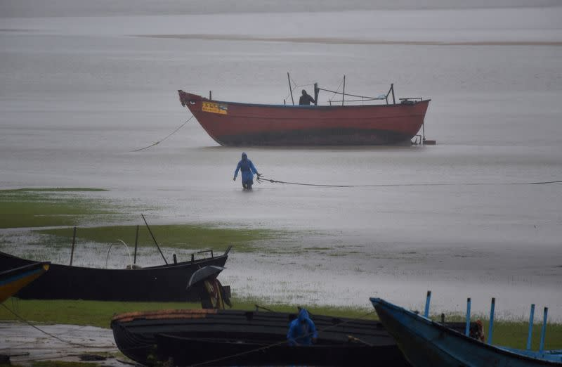 Fishermen tie their boats along the shore before Cyclone Amphan makes its landfall, in the Baleswar district