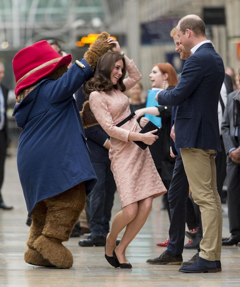 The Duchess got into the swing of things as Prince William and Prince Harry looked on. Photo: Getty Images