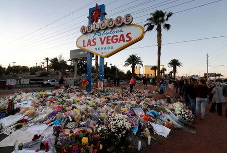 """The """"Welcome to Las Vegas"""" sign is surrounded by flowers and items, left after the October 1 mass shooting, in Las Vegas, Nevada U.S. October 9, 2017. REUTERS/Las Vegas Sun/Steve Marcus"""