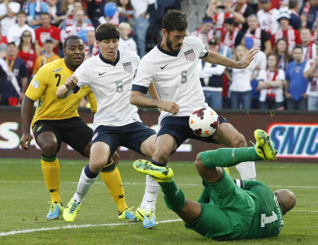 U.S. goalie Tim Howard (1) blocks a shot as United States' Matt Besler (5) and Brad Evans (6) defend in the first half of a World Cup qualifier soccer match at Sporting Park in Kansas City, Kan., Friday, Oct. 11, 2013. At left rear is Jamaica's Westley Morgan. (AP Photo/Colin E. Braley)