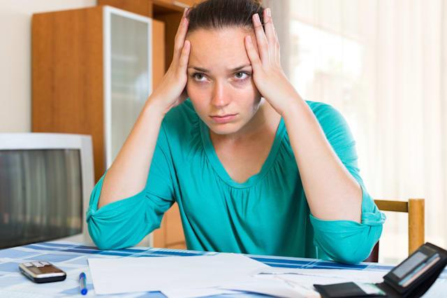 Young woman sitting depressed at the table because of financial problems