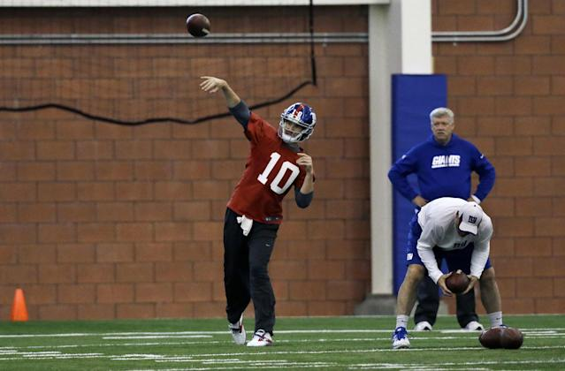 New York Giants offensive coordinator Kevin Gilbride, right, watches as quarterback Eli Manning (10) throws a pass during NFL football practice in East Rutherford, N.J., Wednesday, Nov. 20, 2013. AP Photo/Mel Evans)