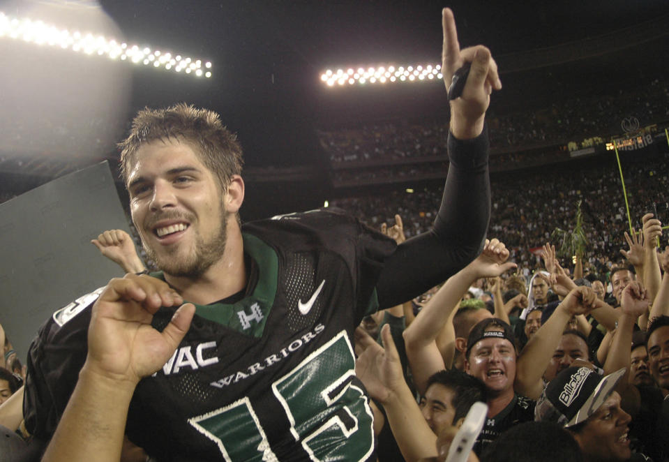 FILE - In this Nov. 23, 2007, file photo, then-Hawaii quarterback Colt Brennan celebrates after an NCAA college football game in Honolulu. Brennan, a star quarterback at the University of Hawaii who finished third in the 2007 Heisman Trophy balloting, died early Tuesday, May 11, 2021, his father said. He was 37. Brennan, who has had public struggles with alcohol, died at a hospital in California, his father, Terry Brennan, told The Associated Press. (AP Photo/Ronen Zilberman, File)