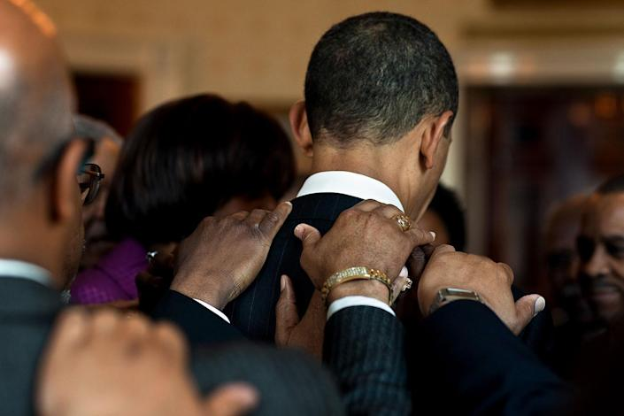 Before a prayer breakfast in 2010, Obama met privately with clergy members in the Blue Room at the White House. At the conclusion of the meeting, a final prayer was delivered as they held each other's shoulders. (Official White House photo by Pete Souza)