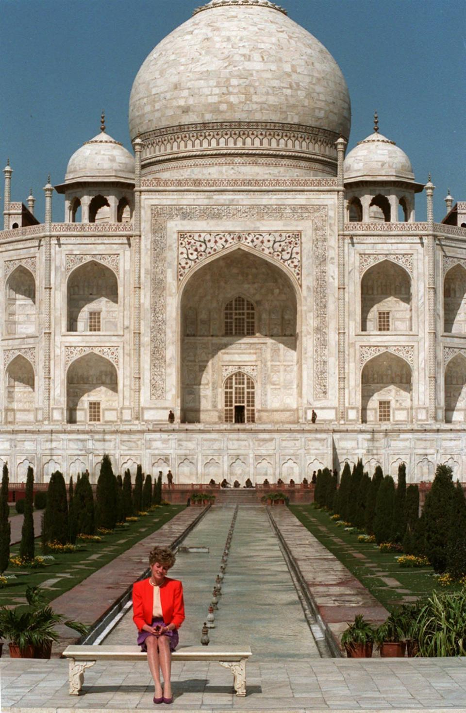"""FILE - In this file photo dated Feb. 11, 1992, Britain's Princess Diana sits alone backdropped by the Taj Mahal in Agra, India. For someone who began her life in the spotlight as """"Shy Di,"""" Princess Diana became an unlikely, revolutionary during her years in the House of Windsor. She helped modernize the monarchy by making it more personal, changing the way the royal family related to people. By interacting more intimately with the public -- kneeling to the level of children, sitting on edge of a patient's hospital bed, writing personal notes to her fans -- she set an example that has been followed by other royals as the monarchy worked to become more human and remain relevant in the 21st century. (AP photo/Udo Weitz, File)"""