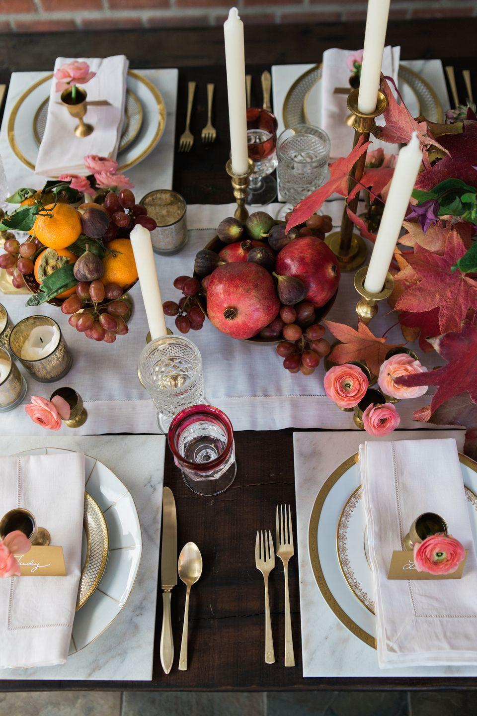 """<p>At a <a href=""""https://www.elledecor.com/life-culture/entertaining/g3396/thanksgiving-hosting-tips-from-professionals/"""" rel=""""nofollow noopener"""" target=""""_blank"""" data-ylk=""""slk:fall dinner"""" class=""""link rapid-noclick-resp"""">fall dinner</a> inspired by childhood memories of playing in the leaves and sharing holiday dinner, <a href=""""http://www.twinkandsis.com/blog/a-thanksgiving-dinner-inspired-by-our-childhood?rq=Thanksgiving"""" rel=""""nofollow noopener"""" target=""""_blank"""" data-ylk=""""slk:Twink + Sis"""" class=""""link rapid-noclick-resp"""">Twink + Sis</a> filled their tablescape with an abundance of pomegranates, tangerines, figs and grapes, with colorful leaves and plenty of long, tapered candles throughout.</p>"""