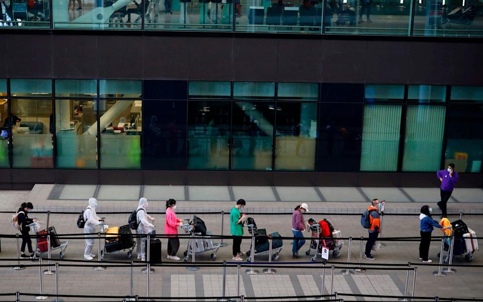 Passengers wearing PPE (personal protective equipment) queue up to board a China bound flight at Terminal 2 of Heathrow airport - AFP