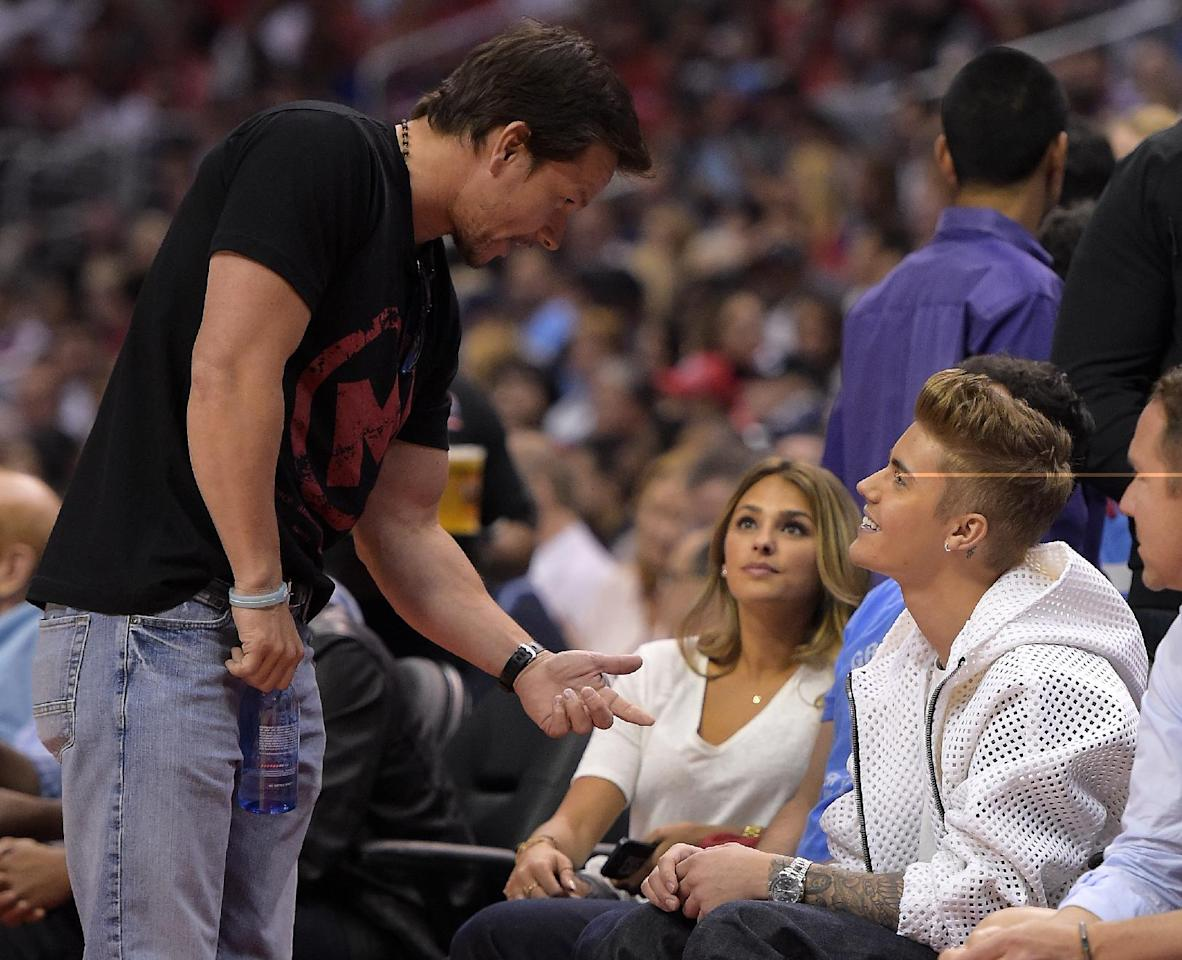 Singer Justin Bieber, right, talks with actor Mark Wahlberg as he watches the Los Angeles Clippers play the Oklahoma City Thunder in the second half of Game 4 of the Western Conference semifinal NBA basketball playoff series, Sunday, May 11, 2014, in Los Angeles. (AP Photo/Mark J. Terrill)