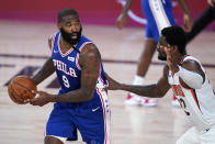 Philadelphia 76ers center Kyle O'Quinn (9) looks for help as Phoenix Suns center Deandre Ayton, right, defends during the first half of an NBA basketball game Tuesday, Aug. 11, 2020, in Lake Buena Vista, Fla. (AP Photo/Ashley Landis, Pool)