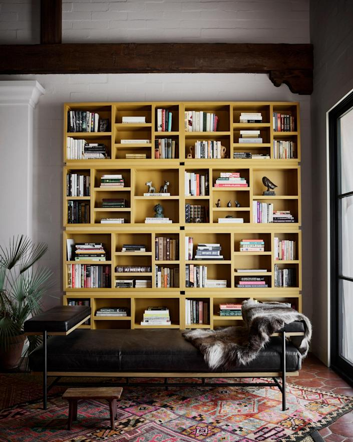 "<div class=""caption""> A custom bookcase anchors one end of the living room. </div>"