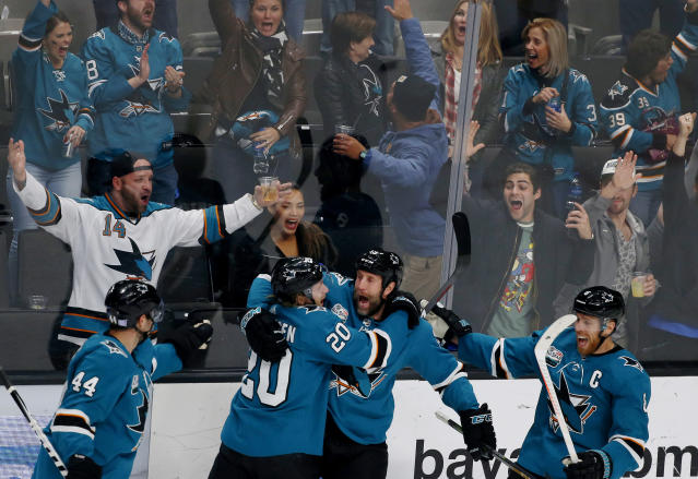 San Jose Sharks' Marc-Edouard Vlasic (44) and Marcus Sorensen (20) celebrate with teammate Joe Thornton, third from left, who scored his 400th career goal in the third period of an NHL hockey game against the Nashville Predators, in San Jose, Calif., Tuesday, Nov. 13, 2018. (AP Photo/Josie Lepe)