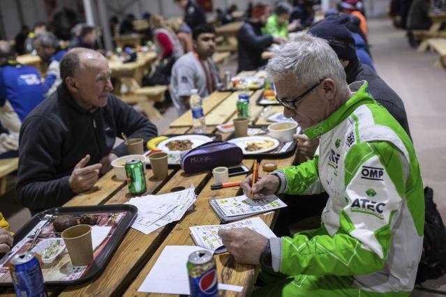 In this Sunday, Jan. 12, 2020 photo, co-driver Maurizio Dominella of Italy, checks the road book for the next stage at the restaurant of the Dakar Rally in Wadi Al Dawasir, Saudi Arabia. Formerly known as the Paris-Dakar Rally, the race was created by Thierry Sabine after he got lost in the Libyan desert in 1977. Until 2008, the rallies raced across Africa, but threats in Mauritania led organizers to cancel that year's event and move it to South America. It has now shifted to Saudi Arabia. The race started on Jan. 5 with 560 drivers and co-drivers, some on motorbikes, others in cars or in trucks. Only 41 are taking part in the Original category. (AP Photo/Bernat Armangue)