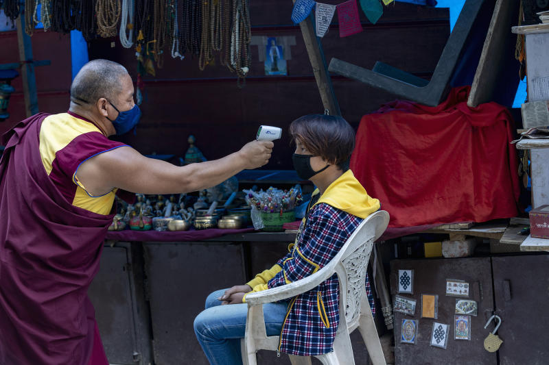 An exile Tibetan Buddhist monk uses a digital probe thermometer to measure the body temperature of a roadside vendor in Dharmsala, India, Sunday, May 24, 2020. The monk has been walking around the town for the past one week checking people's temperature as part of community service amid the COVID-19 pandemic. (AP Photo/Ashwini Bhatia)
