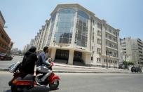 A family rides a motorbike in front of National Hepatology and Tropical Medicine Research Institute amid concerns about the spread of the coronavirus disease (COVID-19), in Cairo