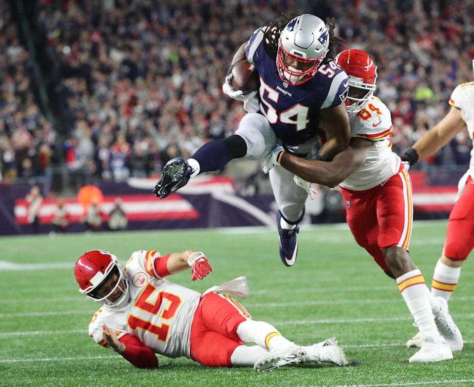 Dont'a Hightower of New England runs back an interception of Patrick Mahomes (15) in Sunday night's game. (Getty)