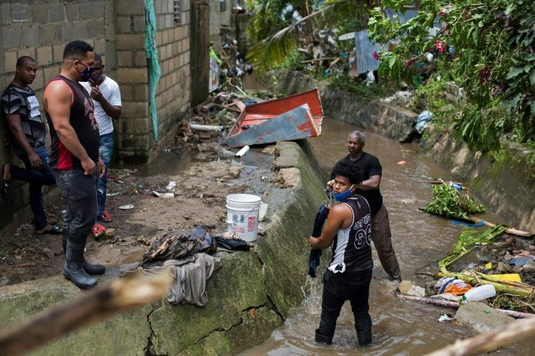 People wash their belongings in a stream after the passage of Isaias, with heavy rain causing the overflowing of the Magua River in Hato Mayor, Dominican Republic, on July 31, 2020 (AFP Photo/Erika SANTELICES)