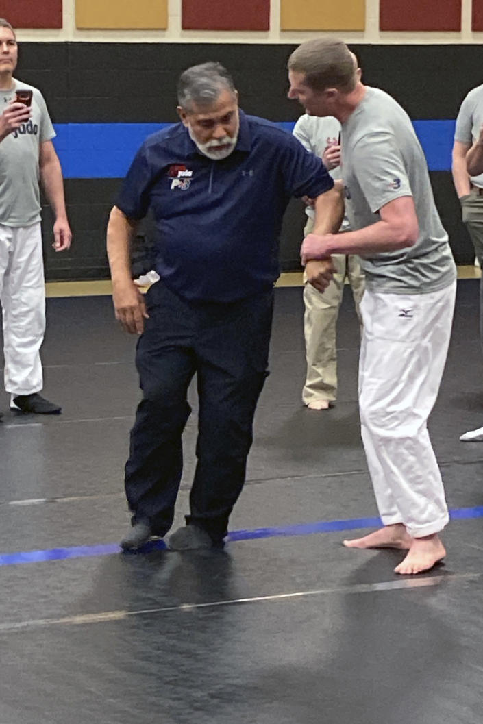 Michael Johnson of the Billings, Montana Police Department grabs hold of instructor Mike Verdugo's arm while Harley Cagle of the Billings, Montana Police Department, left, captures the action on his cell phone during a training workshop on March 9, 2021, in Douglas, Wyoming. USA Judo officials spearheaded the training session to try to give officers techniques that could help them avoid using deadly force when they encounter potential suspects. (AP Photo/Eddie Pells)