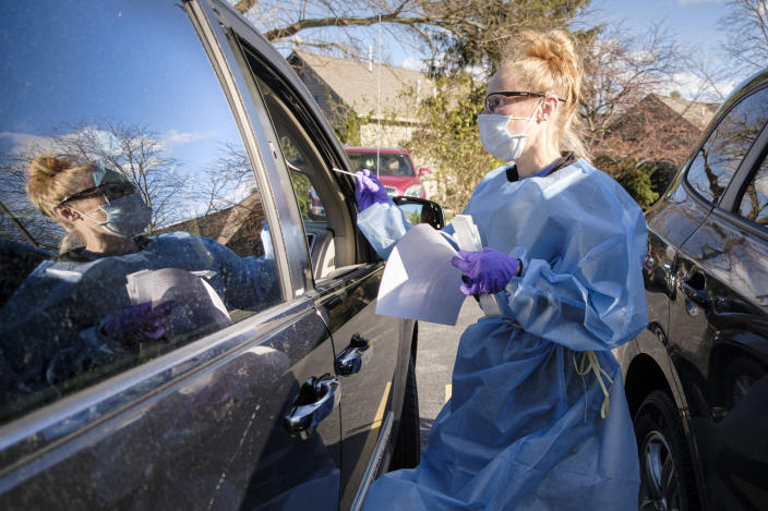 A healthcare worker swabs a patient during a drive-up rapid COVID test on Nov. 15 in West Des Moines, Iowa. (Jack Kurtz/ZUMA Wire)