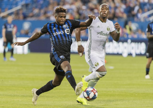 Montreal Impact's Orji Okwonkwo, left, breaks away from Portland Timbers' Claude Dielna during first half of an MLS soccer game in Montreal, Wednesday, June 26, 2019. (Graham Hughes/The Canadian Press via AP)
