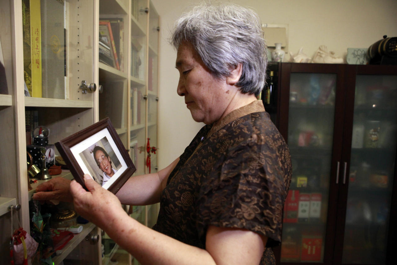 Zhang Xianling holds a photo of her late son, Wang Nan, who was killed in the 1989 Tiananmen Square crackdown during an interview in Beijing, China, Monday, May 28, 2012. Zhang said her friend Ya Weilin, a father of a man killed in the 1989 crackdown had committed suicide on Friday, May 25, 2012 out of despair and to protest the government's long-standing refusal to address the grievances of the victims' relatives. (AP Photo/Ng Han Guan)
