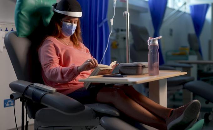 Y Combinator's Summer 2021 Demo Day, Luminate: A woman sits in a chemotherapy clinic in a chair with Luminate's headset on.
